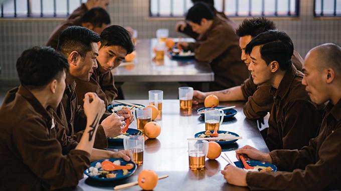 Cổ Thiên Lạc và Lâm Phong (ở giữa bên phải) trong một cảnh quay ăn cơm tại trại giam. Trong tạo hình tù nhân, hai nam diễn viên vẫn thể hiện phong độ và vẻ đẹp trai.