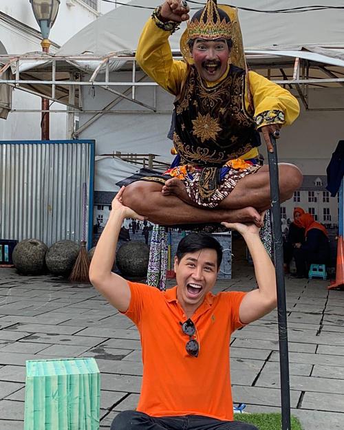 MC Nguyên Khang chụp ảnh cùng người đàn ông làm ảo thuật đường phố ở Indonesia. Nam MC gần đây dính tin đồn phẫu thuật thẩm mỹ cắt mí mắt và nâng mũi vì nhiều khác biệt trên gương mặt. Nhiều khán giả nhận xét thích đôi mắt híp tự nhiên trước đây của anh hơn.