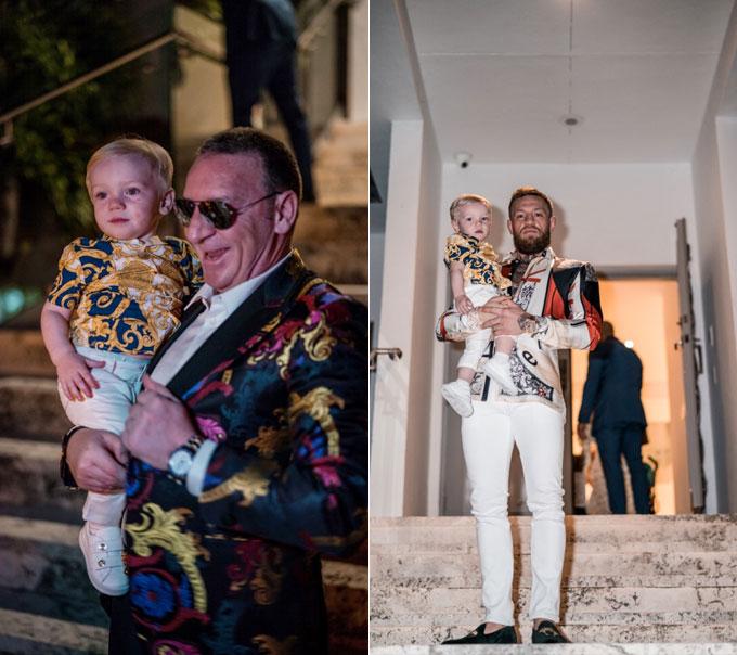 Bé Conor Jr, con trai hơn một tuổicủa McGregor cũng diện một câyVersace, được bố và ông bế trong bữa tiệc.