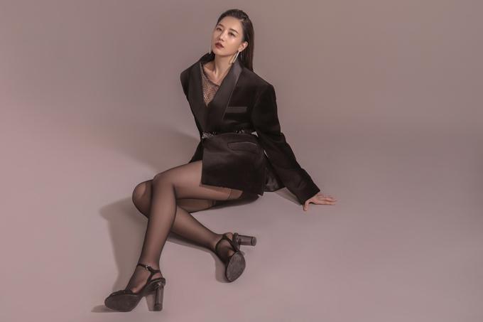 Áo vest với mốt giấu quần giúp cô khoe đôi chân thon dài một cách triệt để. Sự quyến rũ còn được gợi lên từ chiếc áo lưới mỏng manh sau áo vest.