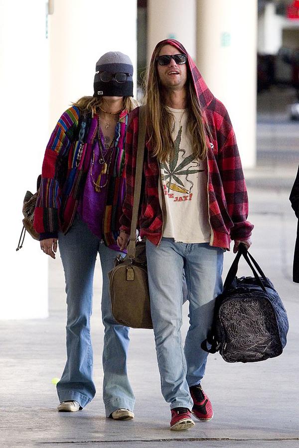 Tuy nhiên khi ra khỏi sân bay, cô đội mũ len kéo kín hết mặt và được bạn trai - rocker Gabriel Glenn - dắt ra chỗ đỗ xe.