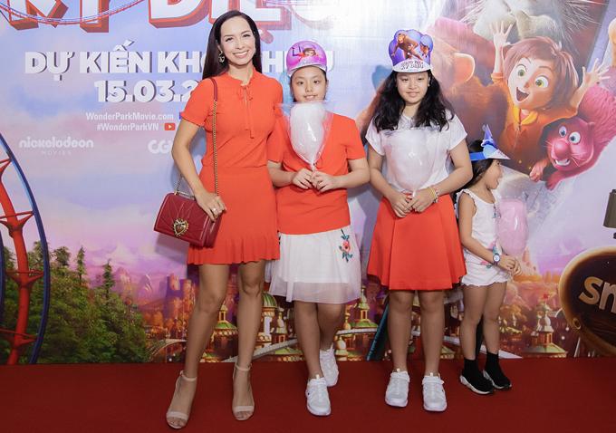 MC Thúy Hạnh mặc trang phục màu cam đồng điệu với hai con gái.