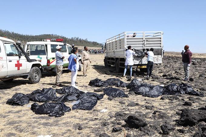 Hiện trường vụ tai nạn máy bay. Nhân viên cứu hộ thu thập các thi thể, bọc trong túi nilon và chuyển đi. Ảnh: AFP.
