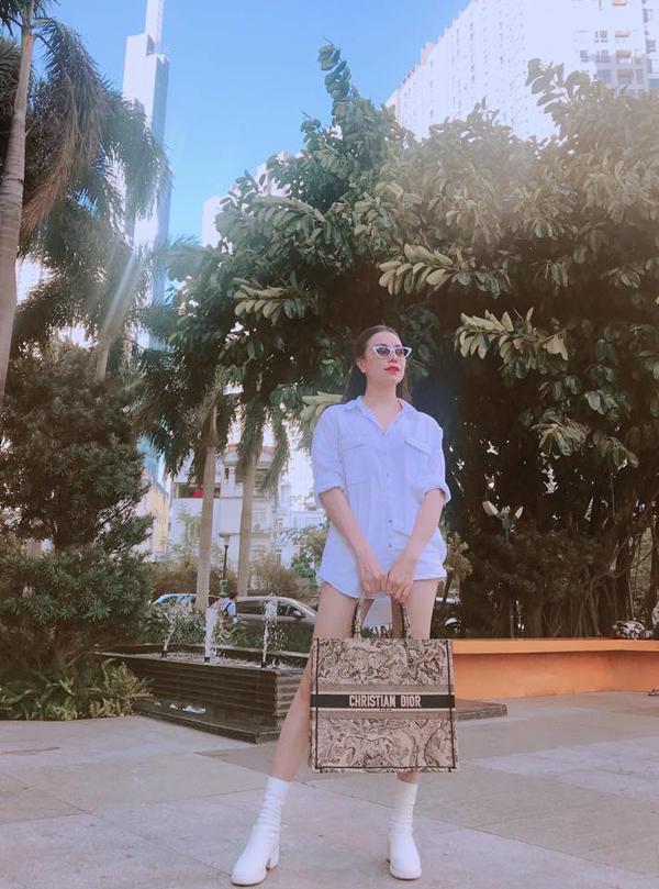 Trà Ngọc Hằng tôn chân dài gợi cảm với mốt giầu quần. Sơ mi trắng được người đẹp diện cùng short jeans. Để giúp bản thân có được phong cách dạo phố bắt mắt, người đẹp đã chọn thêm túi Dior to bản phối cùng bốt trắng cao cổ.