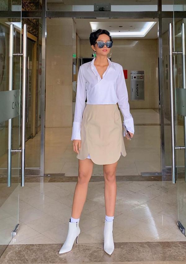 HHen Niê cá tính cùng sơ mi phom dáng rộng kết hợp cùng chân váy ngắn. Kiểu bốt cổ thấp, mũi nhọn hợp mốt được hoa hậu chọn lựa để hoàn thiện set đồ.