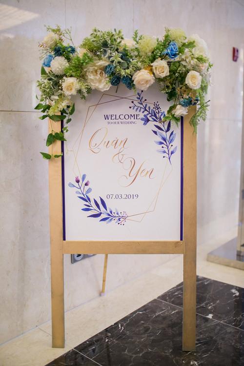 Bảng welcome tiệc cưới có sử dụng họa tiết khối hình học và được tô điểm bởi hoa tươi, mang đến vẻ hiện đại, lãng mạn.