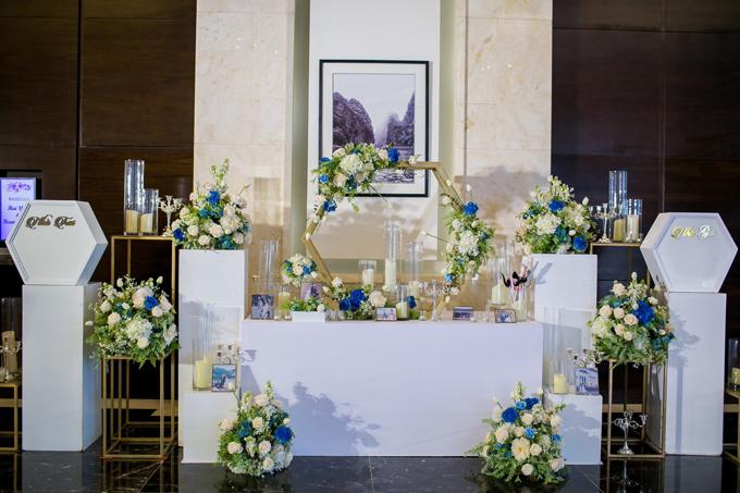 Bàn gallery được trang trí với hoa tươi, ảnh cưới của hai vợ chồng và các khối hình học sơn phủ màu vàng đồng.