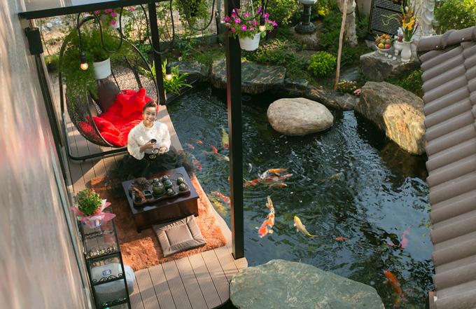 Cô kê bàn uống trà bên cạnh hồ cá koi để vừa thưởng trà vừa ngắm những chú cá đủ màu sắc bơi lội tung tăng.