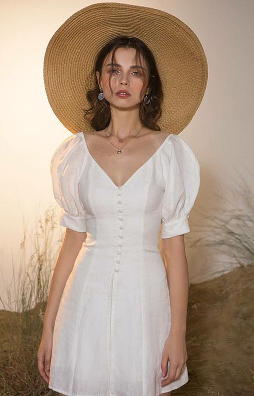Váy cao qua gối được thêm các điểm nhấn xinh xắn ở cổ áo chữ V, tay bồng và đặc biệt là hàng nút bọc vải điệu đà.