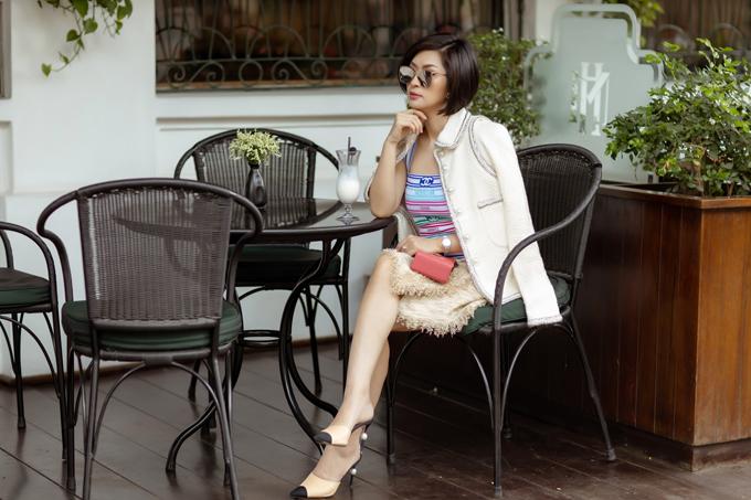 Ca sĩ chọn nguyên set đồ Chanel khi đi cà phê ở Sài Gòn. Áo khoác và chân váy vải tweed đồng điệu được mix cùng áo thun kẻ sọc trẻ trung.