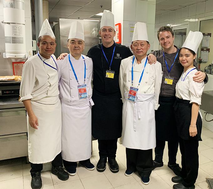 Bếp trưởng Paul Smart chụp ảnh lưu niệm cùng đầu bếp Triều Tiên, phiên dịch và người giám sát của 2 phía.