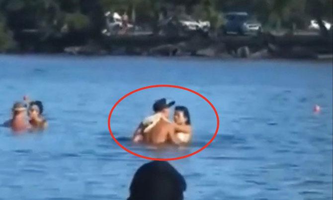 Cô gái và bạn trai ôm ấp nhau khi đang tắm biển.