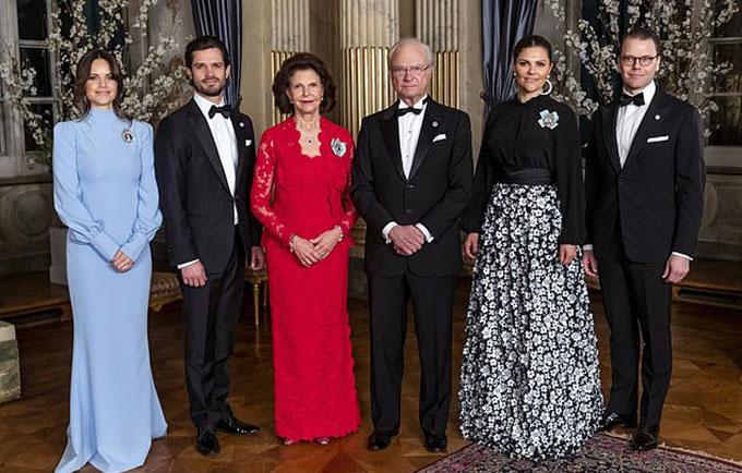 Vua Carl, Hoàng hậu Silvia (váy đỏ), vợ chồng Công chúa Victoria (bên phải) và vợ chồng Hoàng tử Philip (bên trái) tại cung điện ở Stockholm tối 14/3. Ảnh: Backgrid.