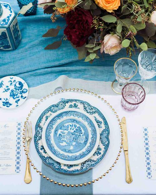 Đĩa ăn của khách có họa tiết truyền thốngphương Đông, mang gam màu xanh lam. Bộ dao nĩa đi kèm được mạ vàng đồng đem đếnâm hưởng hoàng gia.