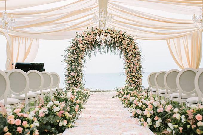 Rạp cưới của uyên ương có cổng cưới hình vòm, được tô điểm bởi hoa hồng tươi.