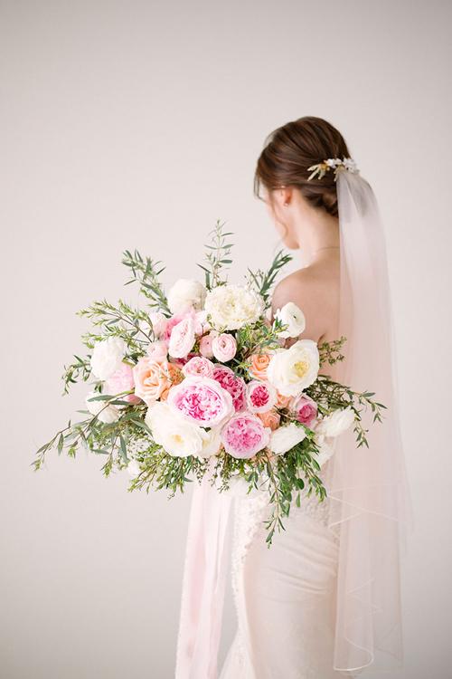 Hoa cầm tay cô dâu được kết từ hoa hồng, hồng leo và các loại lá cây phụ trợ.