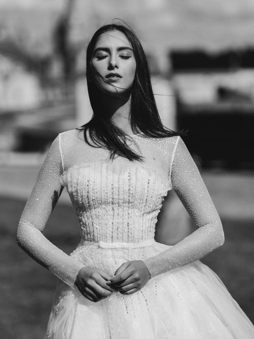 Mẫu váy trắng mang phom dáng đơn giản nhưng có điểm nhấn là những hạt pha lê, đá lấp lánh để tôn lên vẻ đẹp dịu dàng của cô dâu. Việc sử dụng vải xuyên thấu cho phần cánh tay mang đến vẻ quyến rũ khó cưỡng cho bất kỳ cô gái nào khi khoác lên mình bộ đầm cưới này.