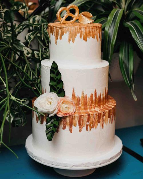 Bánh cưới được phủ vệt trang trí màu vàng đồng theo xu hướng trang trí hiện đại. Phía trên cùng của chiếc bánh là một biểu tượng bánh quy - tượng trưng cho vùng đất mà cô dâu từng lớn lênvà bánh may mắn của người Trung Quốc.