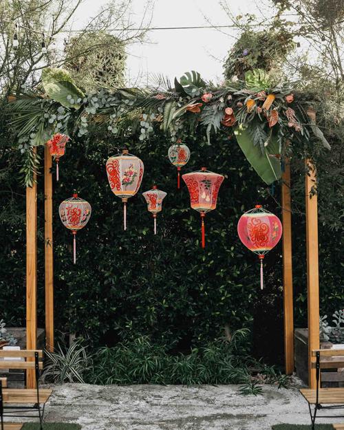 Cổng cưới ở khu vực làm nghi lễ được trang trí bởi hồng môn, monstera, những chiếc đèn lồng xinh xắn của người Trung Quốc.