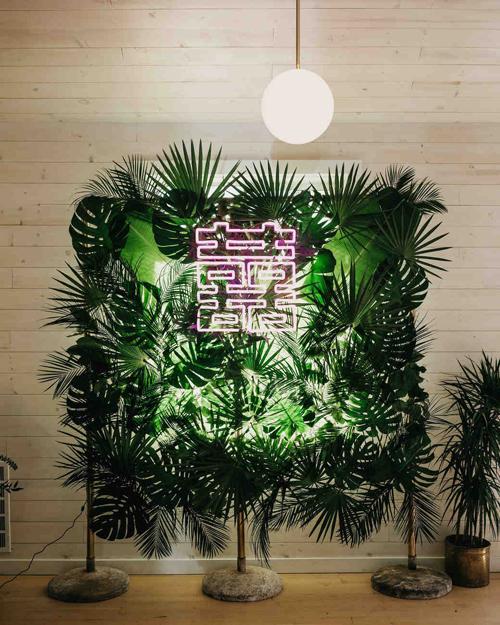 Khu vực photobooth được trang trí bởi lá cọ, lá monstera và chữ hỉ ghép từ đèn neon màu hồng.