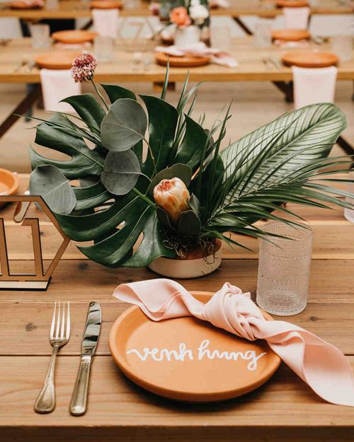 Đĩa ăn của khách mời được đặt một chiếc khăn ăn màu hồng theo sở thích của cô dâu. Đặc biệt, từng chiếc đĩa đều có khắc tên của khách mời bằng laser.