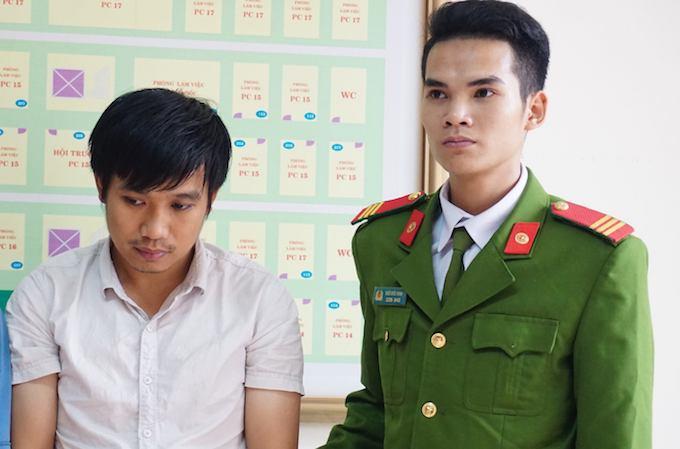 Trần Quang Thành (áo trắng) tại cơ quan điều tra.