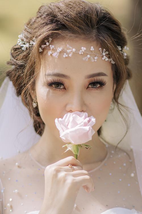 Lối trang điểm trong trẻo được áp dụngvới hàng chân mày sắc nét và phấn mắt hồng làm toát lên vẻ rạng rỡ của tân nương.