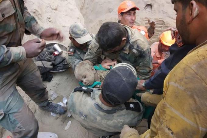 Cậu bé người đầy đất cát khi được bế ra khỏi giếng. Ảnh: Barcroft Media.