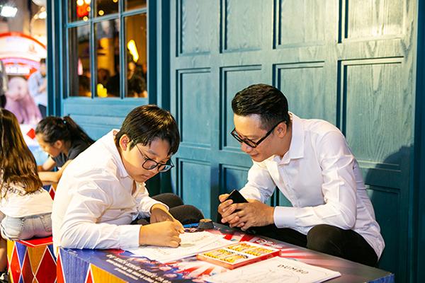 Sự kiện diễn ra vào ngày chủ nhật, thu hút sự tham gia của nhiều gia đình nghệ sĩ. Trong ảnh là ca sĩ Hoàng Bách quan sát con trai Tê Giác vẽ tranh trong buổi ra mắt phim.