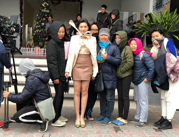 Nữ diễn viên mặc váy áo mỏng manh trong khi các thành phần khác trong đoàn làm phim quàng khăn ấm, đội mũ và mặc nhiều lớp áo khoác dày.