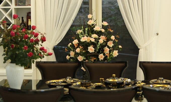 Anh sắm sofa, bàn ăn và bát đĩa màu nâu gỗ để các món nội thất nổi bật trên nền tường trắng sáng.
