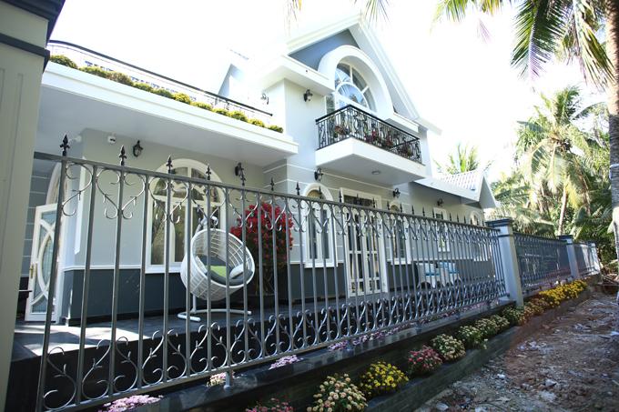 Ngôi nhà có diện tích 500 m2 xung quanh được baophủ bởi bóng mát của những hàng dừa và trang trí hoa cảnh đủ màu sinh động.