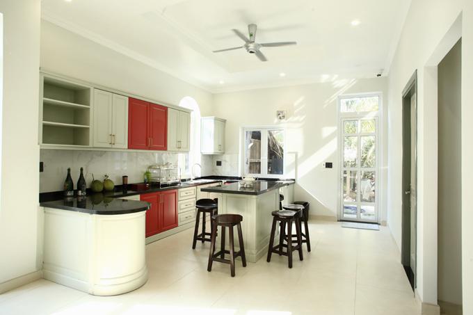 Phòng bếp hiện đại, tiện nghi mang tông màu trắng chủ đạo, điểm xuyết thêm chút gam đỏ nổi bật.