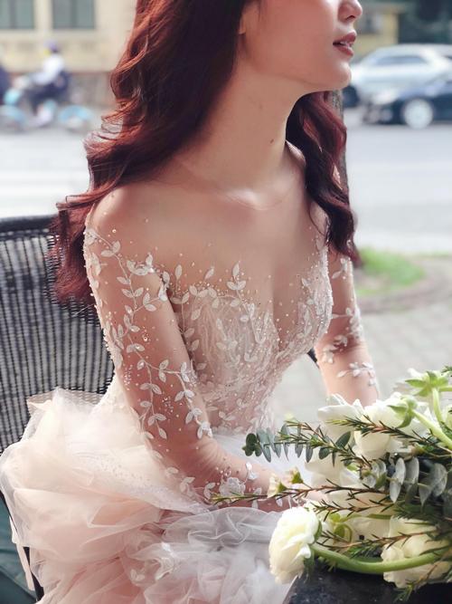 Chiếc váy của Kat được may bằng vải ren Pháp, họa tiết hoa dây leo mềm mại. Trên những chiếc lá, nhà thiết kế còn điểm vài hạt pha lê, vừa để tạo hiệu ứng bắt sáng vừa gợi sự liên tưởng đến hạt sương đọng trên lá buổi sớm mai.