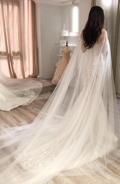 Chiếc áo choàng có độ mềm mại, tạo nét mong manh cho cô dâu mới. Những dải ren lá nhỏ được đính kết một cách tự nhiên, không sắp đặt, phản ánh tính cách phóng khoángcủa cô dâu.