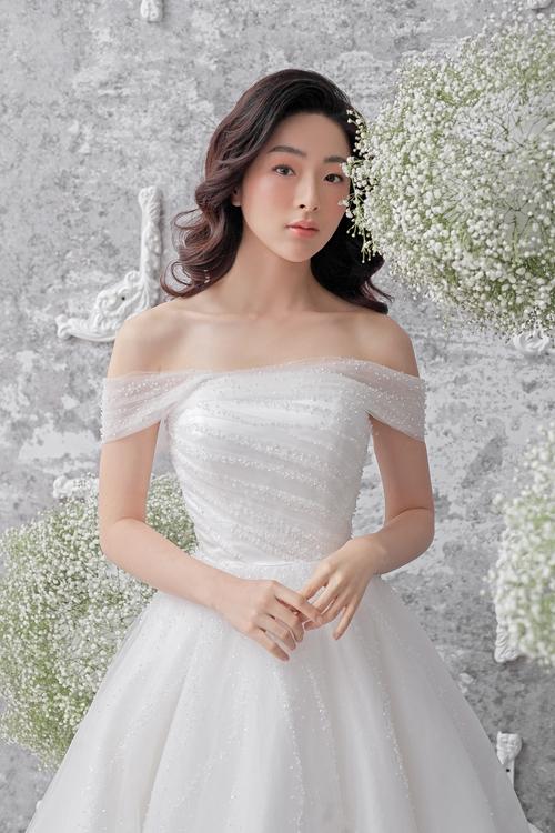 Đầmtheo xu hướng tối giản tiếp tục chiếm lĩnh làng mốt cưới, thích hợp với cô dâu chuộng sự đơn giản, tinh tế. Bộ váy có thiết kế trễ vai, được đính kết hạt đá nhỏ li tigiúp cô dâu tự tin tỏa sáng, thể hiện phong cách của bản thân.