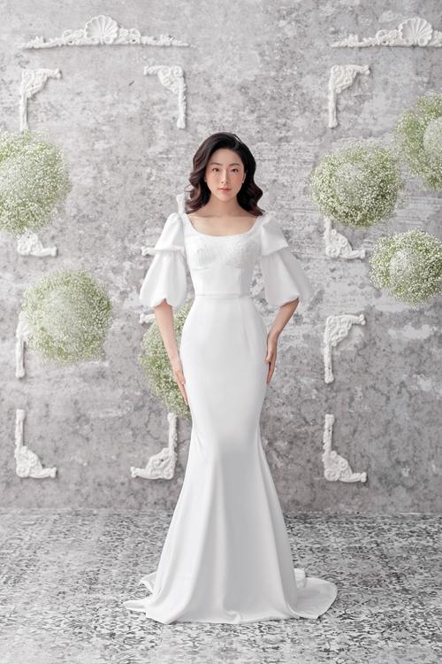 Bộ đầm đuôi cá có thiết kế tay áo phồng theo tầng bậc, tạo hiệu ứng về một chiếc váy tựa bông hoa đang hé nở. Thiết kế cách tân này dễ dàng chiều lòng nàng dâu, giúp phái đẹp có được vẻ đẹp dịu dàng, e lệ.