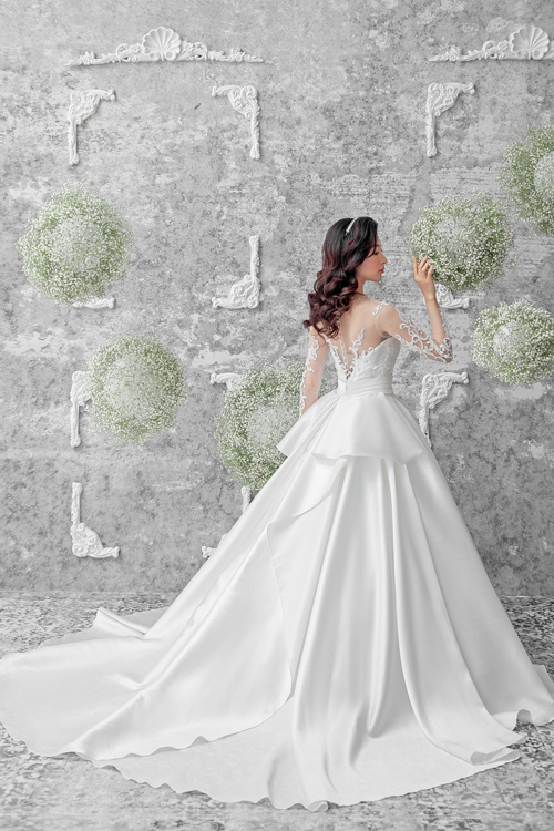 Phần lưng váy được chú trọng như cách mà nhà mốt đã quan tâm đến mặt trước của váy. Đằng sau lưng là tổng hòa của lớp vải ren, voan mỏng và chất liệu satin cùng hàng cúc ngọc trai. Riêng phần eo được điểm thêm tà phụ,tạo sự khác biệt cho mẫu váy mang phom dáng cổ điển.