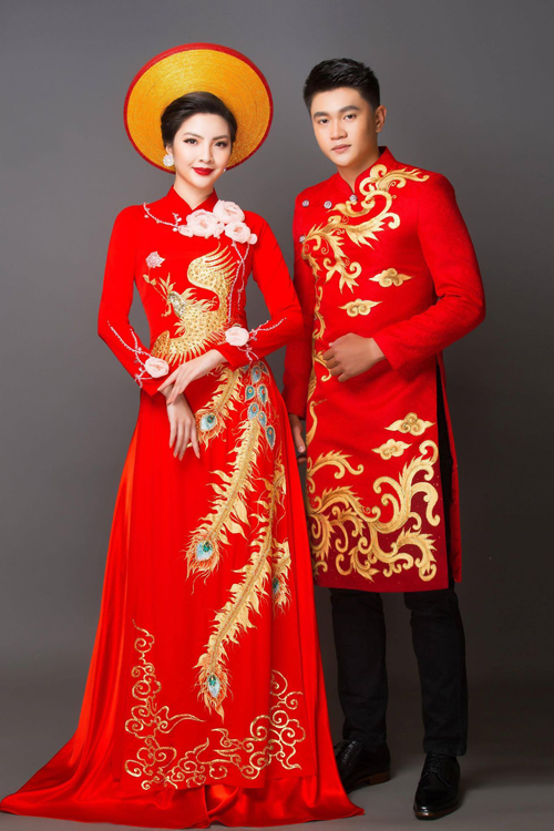 Áo dài cưới màu đỏ mang đến sự sang trọng với chất liệu vải cao cấp. Sự đồng điệu trong trang phục của cô dâu chú rể thể hiện ở họa tiết màu vàng đồng mang đậm nét văn hóa Á đông.
