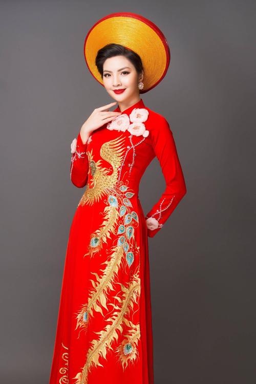 Tà áo dài lụa đỏ của cô dâu được điểm cánh hoa 3D để tăng sự nữ tính. Họa tiết chim công được lựa chọn để tô điểm cho tấm áo và giúp cô dâu trở nên cao ráo hơn.