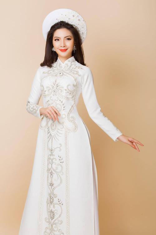 Mẫu áo dài cô dâu có họa tiết chạy dọc thân và được kết hạt tạo sự nổi bật.
