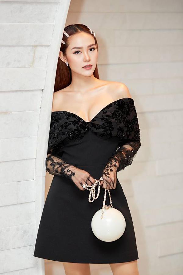 Bé Heo khong diện váy dạ hội cắt xẻ cao, thay vào đó là mẫu váy trễ vai được trang trí họa tiết tiệp màu. Bộ cánh vừa tôn nét gợi cảm vừa xây dựng hình ảnh trẻ trung, hiện đại cho người mặc.
