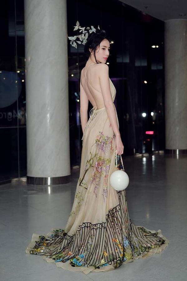 Ca sĩ Thủy Tiên với tạo hình tiên nữ khi diện váy dạ hội, đầu trang trí hoa lá và cầm túi ngọc đi sự kiện.