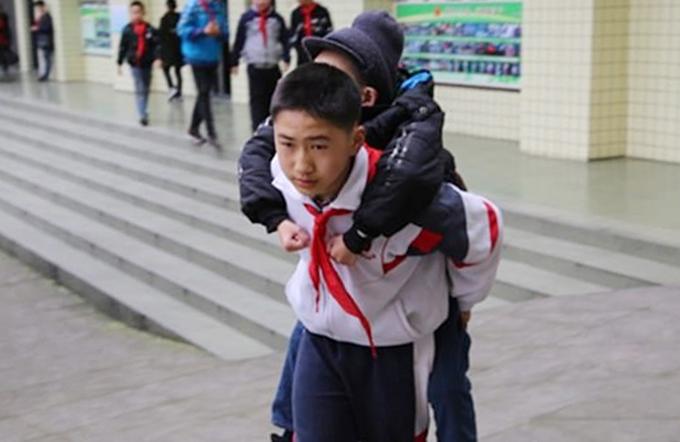 Xu Bingyang (12 tuổi) cõng Zhang Ze đến trường Tiểu học thị trấn Hà Bá, huyện Thanh Thần, thành phố Mi Sơn, tỉnh Tứ Xuyên mỗi ngày. Ảnh: Sinchuan Online.