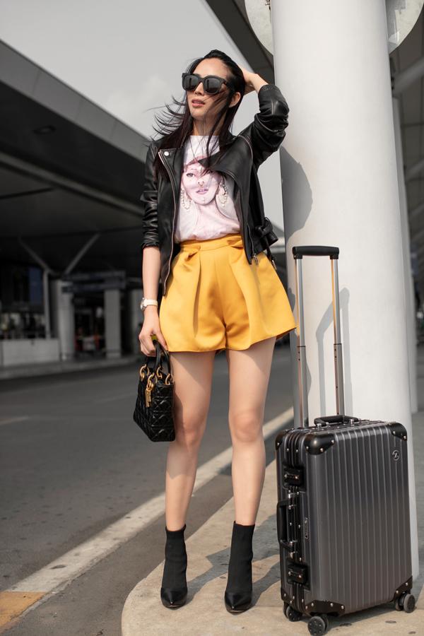 Jacket da đen được người đẹp chọn lựa để sử dụng cùng áo thun in họa tiết, short lụa màu vàng rực rỡ.