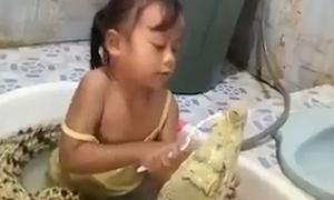 Bé gái tắm và đánh răng cho cá sấu