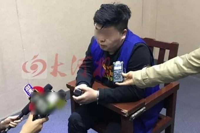 Tan - nghi phạm lừa tình lừa tiền của 19 phụ nữ - bị bắt ở đồn cảnh sát Hà Nam, Trung Quốc hôm 22/3. Ảnh: Weibo.