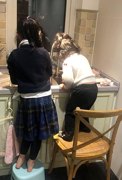 Hai chị em được mẹ chuẩn bị cho ghế để đứng lên khi rửa rau, bát.