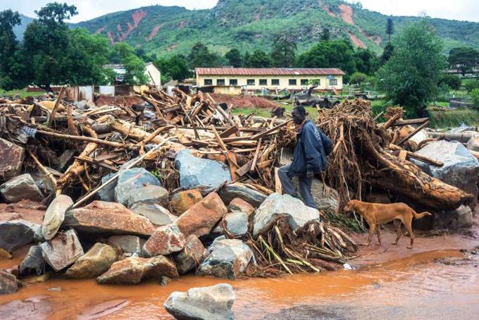 Một người đàn ông Zimbabwe dẫn cho đi tìm người thân trong đống đổ nát do bão Idai. Ảnh: AFP.