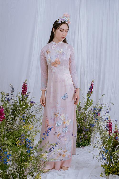 NTK đã tái hiện khu vườn mù hạ với cánh bướm by lượn trên tà áo. Phần ty áo trở nên ngắn hơn so với áo dài truyền thống, phù hợp với nhịp sống hiện đại.